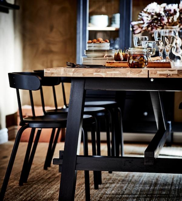 Una taula de menjador d'acàcia SKOGSTA amb potes negres i cadires YNGVAR en antracita sobre una catifa de jute. La taula està parada.