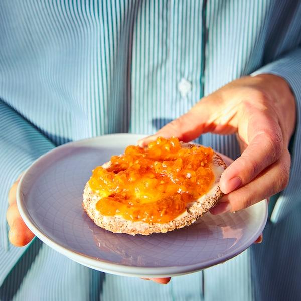 Egy fehér tányért tartó kéz, a tányéron pedig egy törpemálna lekváros kenyér látható.