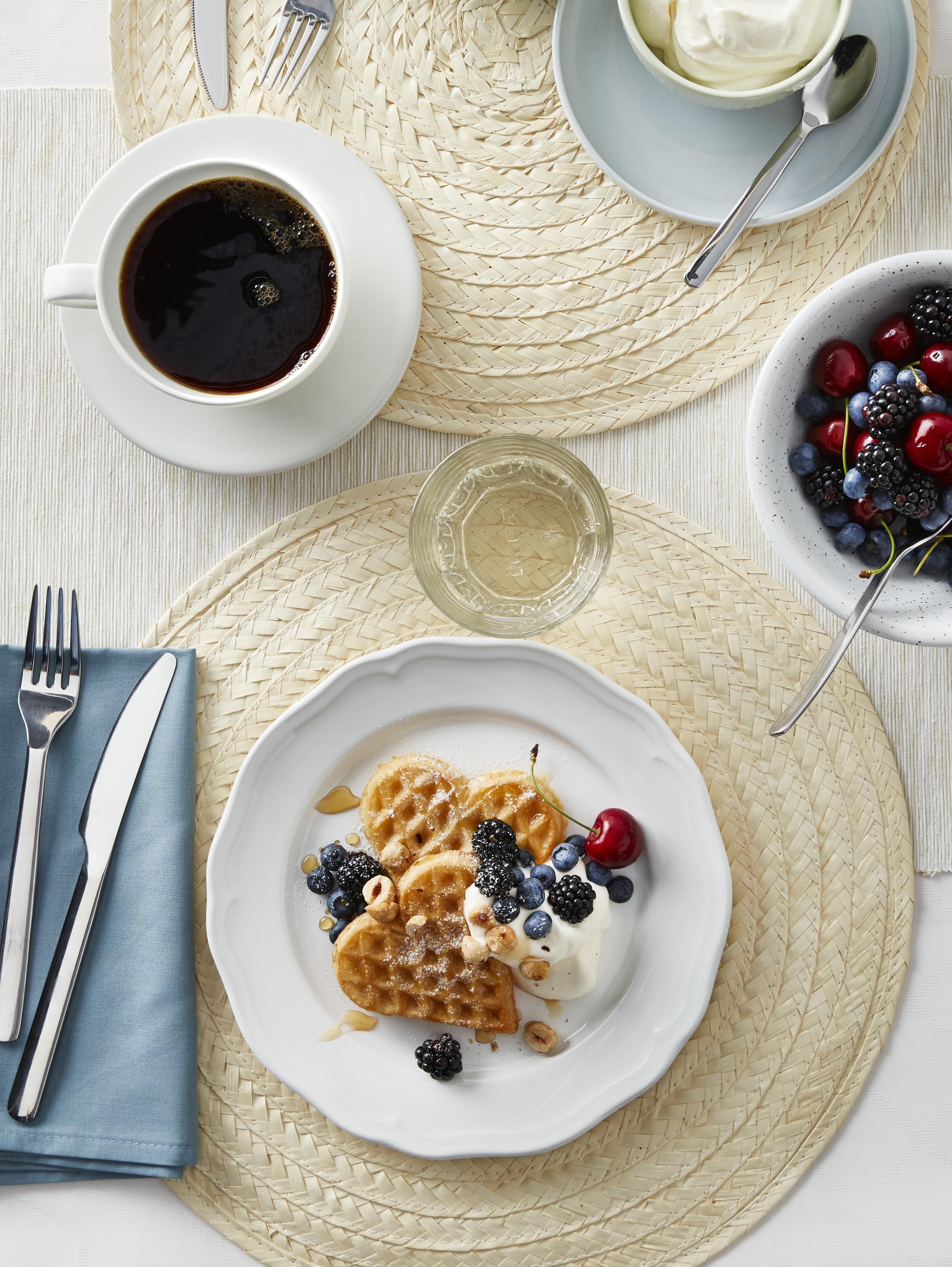 Stol sa četiri SLUTEN podmetača na njemu. Na njima su plave zdjele i tanjuri puni hrane, šalice kave i pribor za jelo.