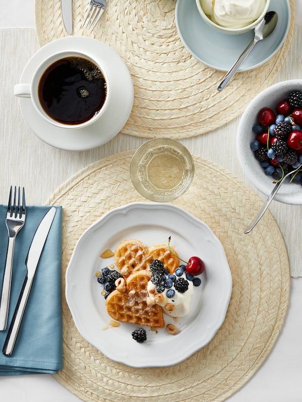 O farfurie ARV albă cu vafe, fructe și frișcă este așezată pe un suport de farfurii SLUTEN pe o masă cu alte articole de masă.