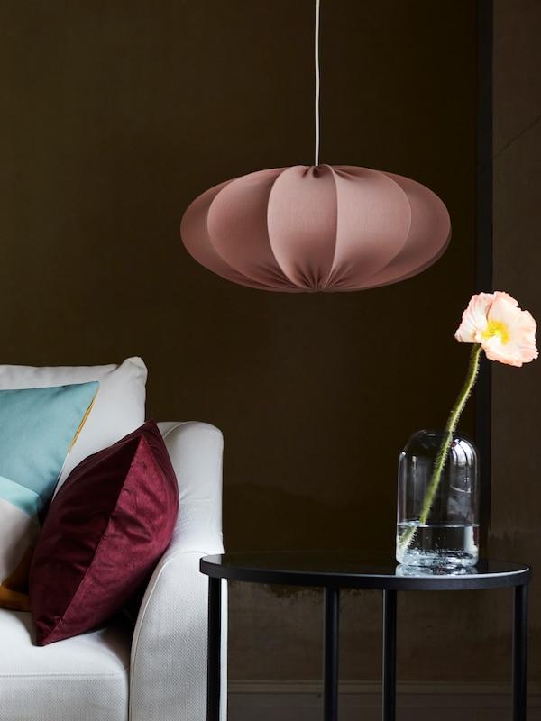 Helle Kissen befinden sich auf einem weißen FÄRLÖV Sofa neben einem schwarzen Beistelltisch. Eine REGNSKUR Hängeleuchte hängt daneben.