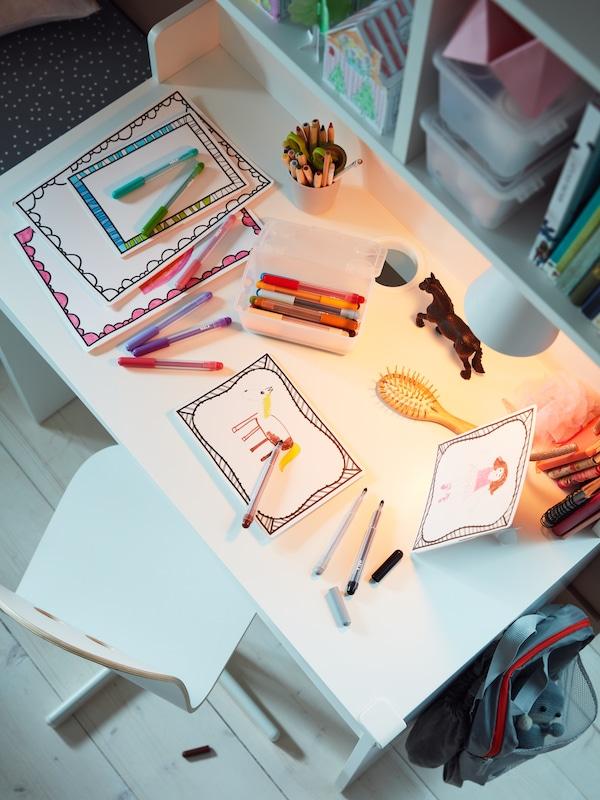 Et hvidt skrivebord, en hvid juniorstol, tuscher, tegnekarton i ramme, en hårbørste og bøger.
