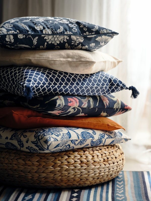 Stacked cushions, among them one with an IDALINNEA cover, on an ALSEDA banana-fiber stool standing on a multicolor rug.