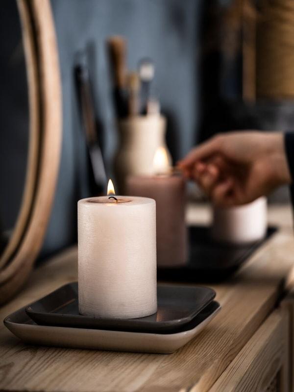 Une main allume une bougie LUGGA qui repose sur une assiette carrée.