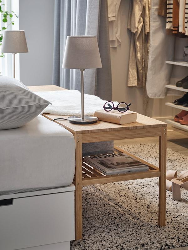 Un banc NORDKISA en bambou est placé à côté d'un lit et sert de table de chevet, alors que des lampes de table, des lunettes et un livre sont placés dessus.