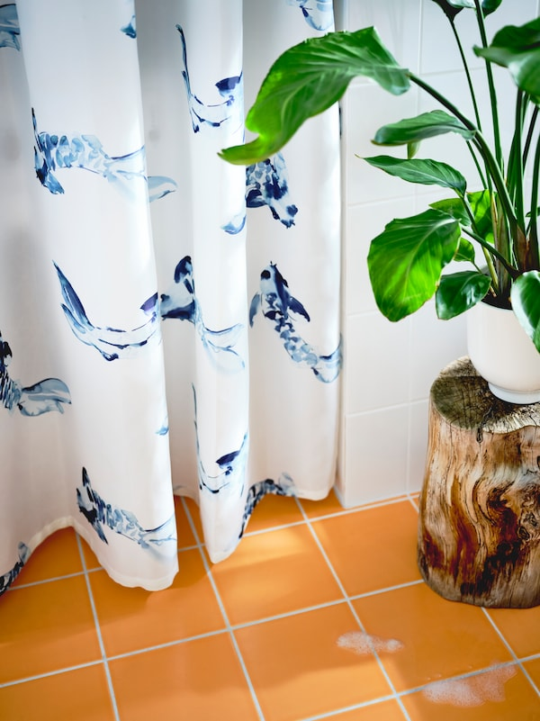 A white and blue VATTENSJÖN shower curtain with a fish motif and a green plant standing next to the shower in a bathroom.