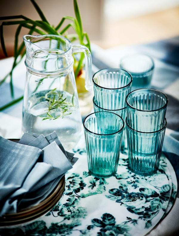 Copos verdes empilhados sob um individual florido verde e branco, junto a um jarro com água.