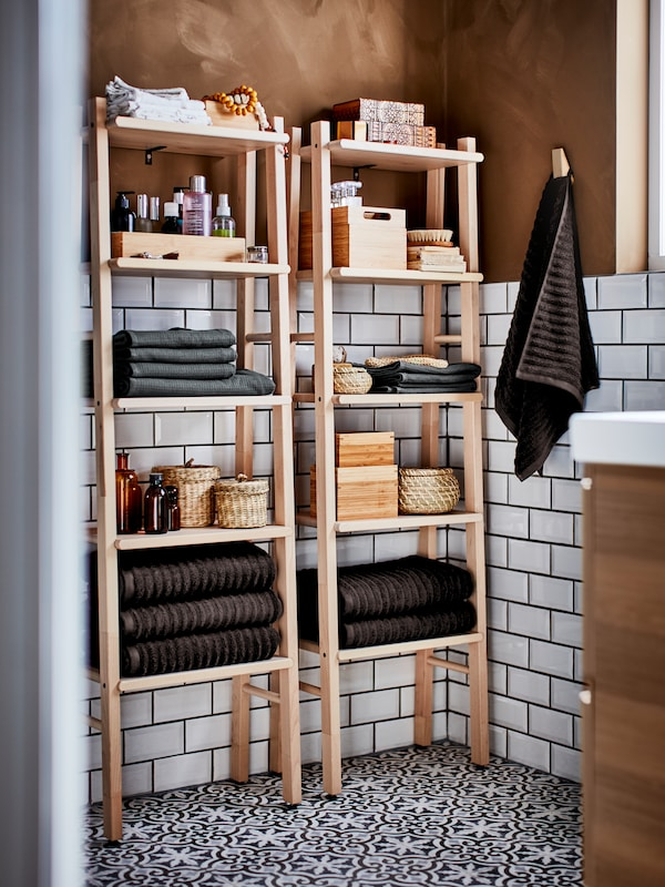 A bright, white tiled bathroom with two shelving units in birch stocked with towels, beauty products and boxes.