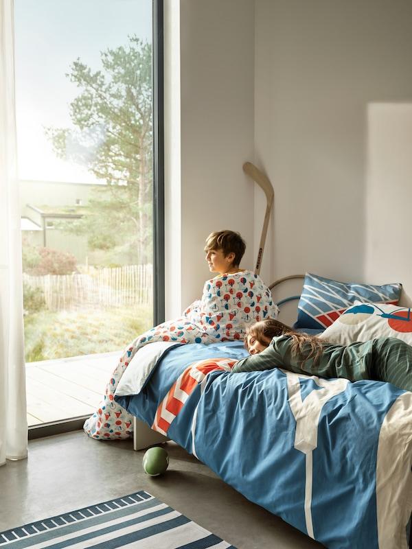 Twee kinderen op bed, met SPORTSLIG lakens