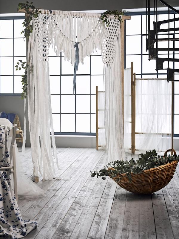 Un cenador de boda con tela azul y blanca colgada de un marco de madera, y una cesta TÄNKVÄRD con plantas artificiales.