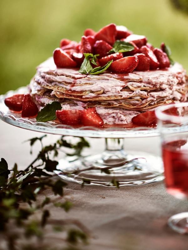 Un gâteau constitué de crêpes empilées recouvertes de fraises, servi sur un plat de présentation en verre transparent.