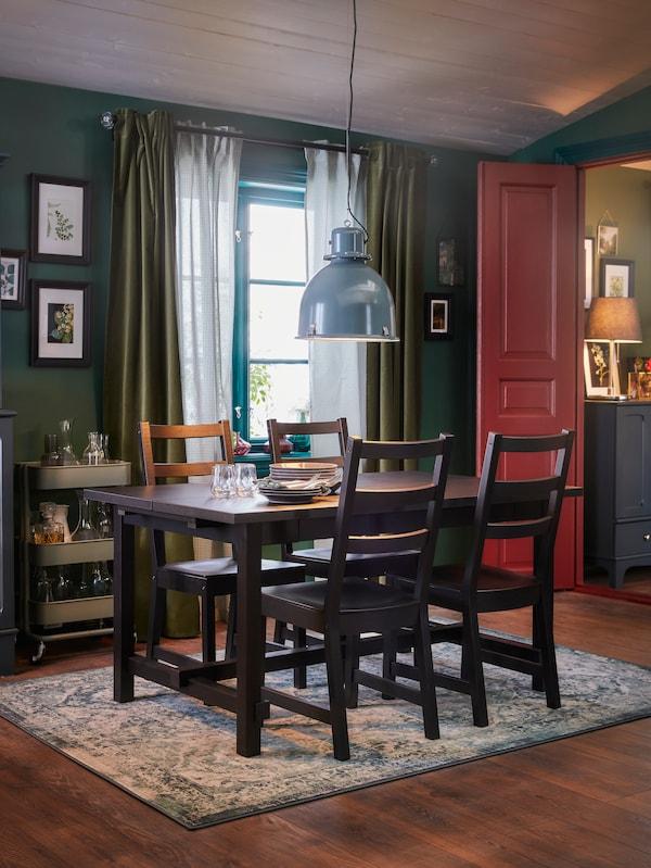 Une salle à manger avec une table et quatre chaises noires, un tapis d'Orient et une suspension gris-turquoise.
