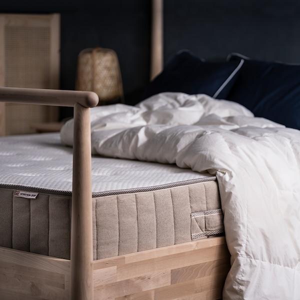 Puinen sänky jolla on VATNESTRÖM-patja ja peitto ilman lakanoita.