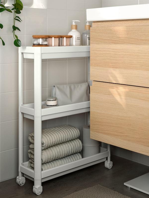 Ljust badrum med en smal rullvagn för smart förvaring i trånga utrymmen.