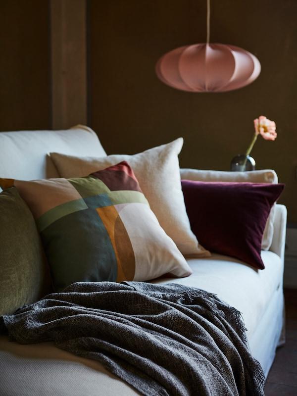 쿠션과 담요, 조명, 꽃병이 있는 소파의 모습.