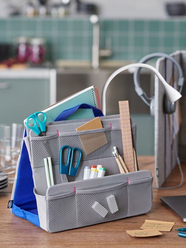 A desktop with an ÖVNING organiser filled with office accessories, standing next to an ÖVNING desk divider.