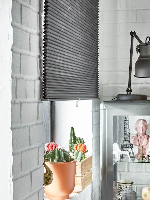 A light grey GUNRID air purifying curtain hangs in front of a sunlit window next to some pampas grass in a vase.