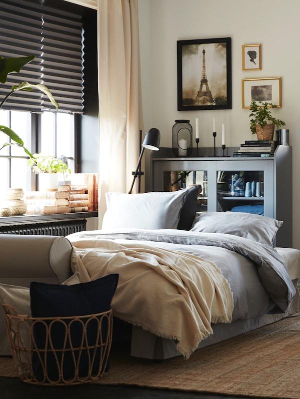 Un canapé-lit beige clair converti en lit avec de la literie grise. Derrière, une vitrine et un tapis en jute sur le sol.