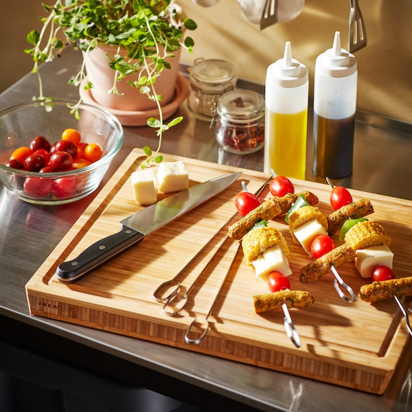 A wooden butcher's block with a knife and vegetable skewers.