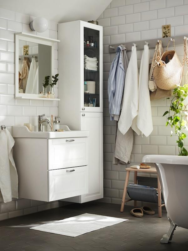 حمام أبيض به وحدة حوض غسل بيضاء مع درجين أسفل مرآة بيضاء مع رف بجوار خزانة مرتفعة بيضاء.