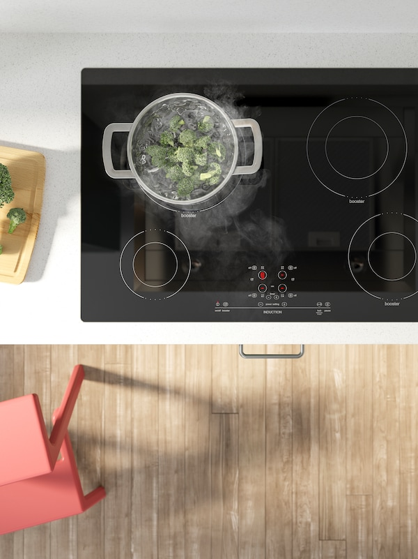 A black NUTID induction cooktop, on a white worktop with marble effect, cooking broccoli in a stainless-steel pot.