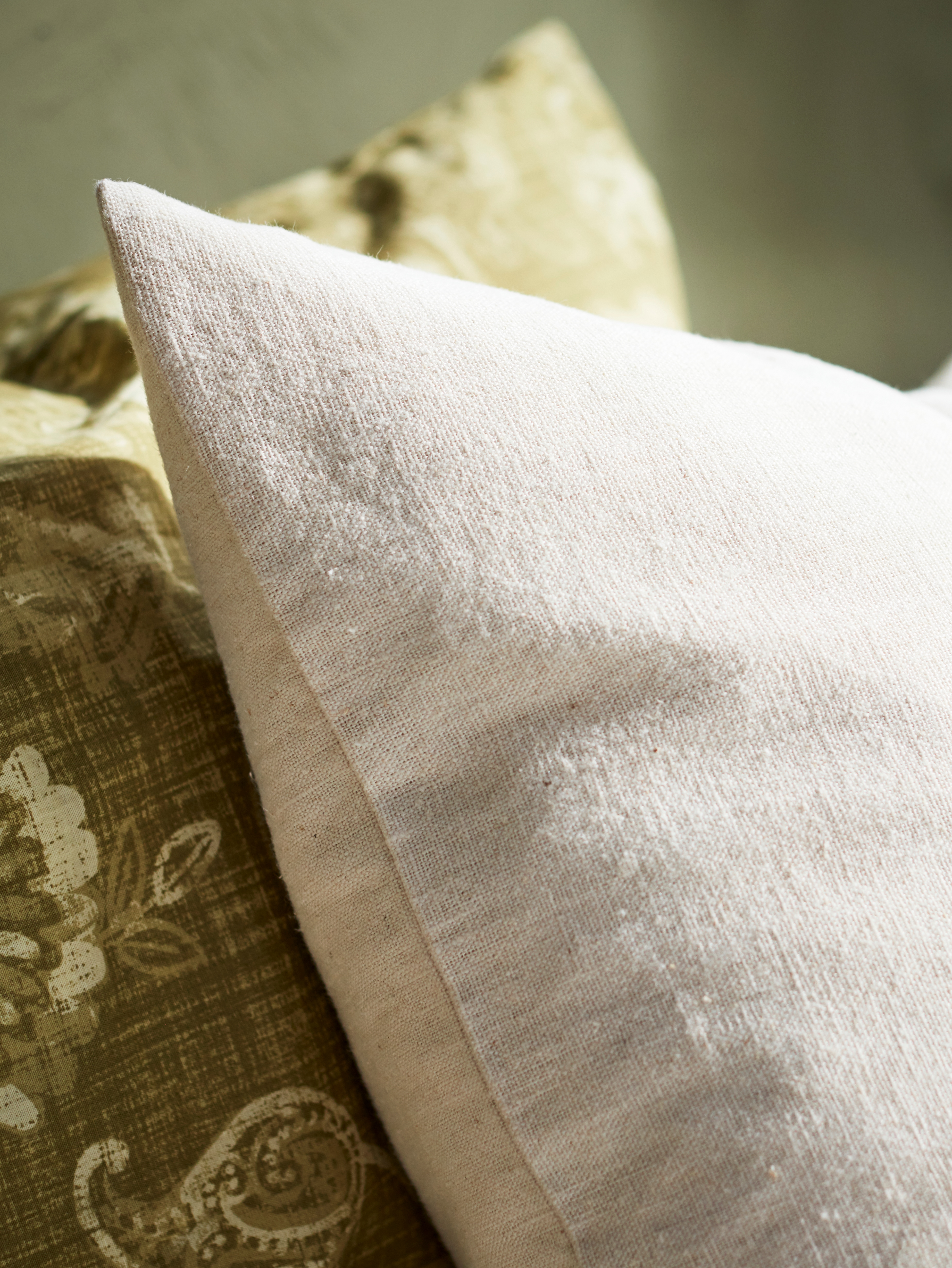 A close-up of a corner of a cushion with a natural VIGDIS cushion cover, showing the slightly irregular texture of its ramie.