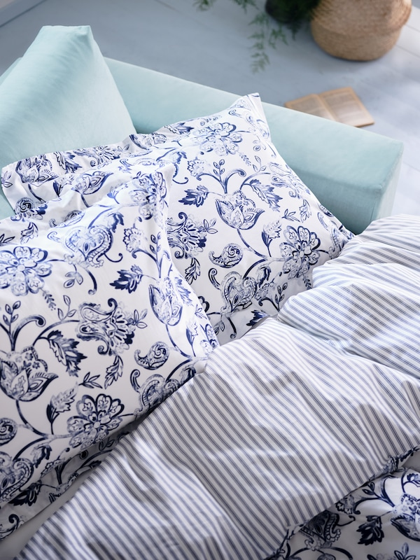 Egy kanapéágy sarka, amely JUNIMAGNOLIA paplanhuzattal és egy fehér/sötétkék virágmintás párnahuzattal van beágyazva.