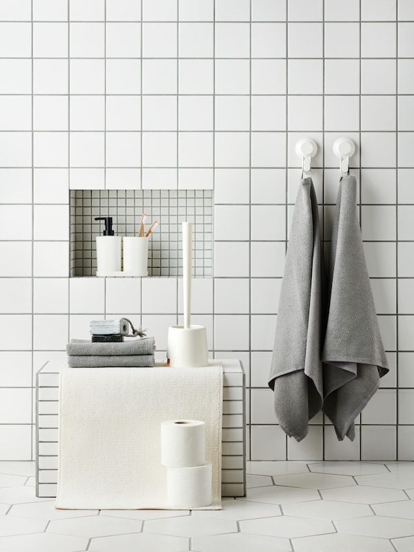 A white-tiled bathroom with grey towels hung on the wall and toiletries placed in a niche.