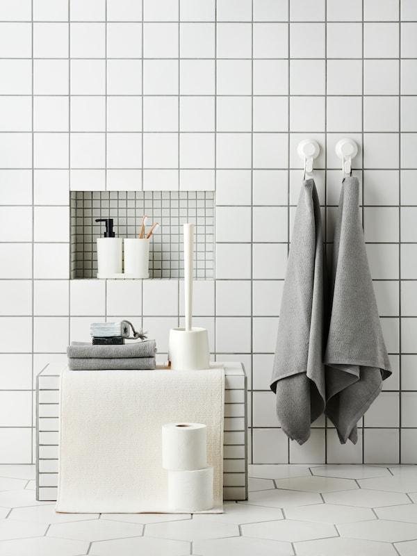 Une salle de bains aux carreaux blancs dans laquelle se trouvent des serviettes grises accrochées au mur, des serviettes grises empilées sur un tabouret et des accessoires STORAVAN posés dans un renfoncement du mur.
