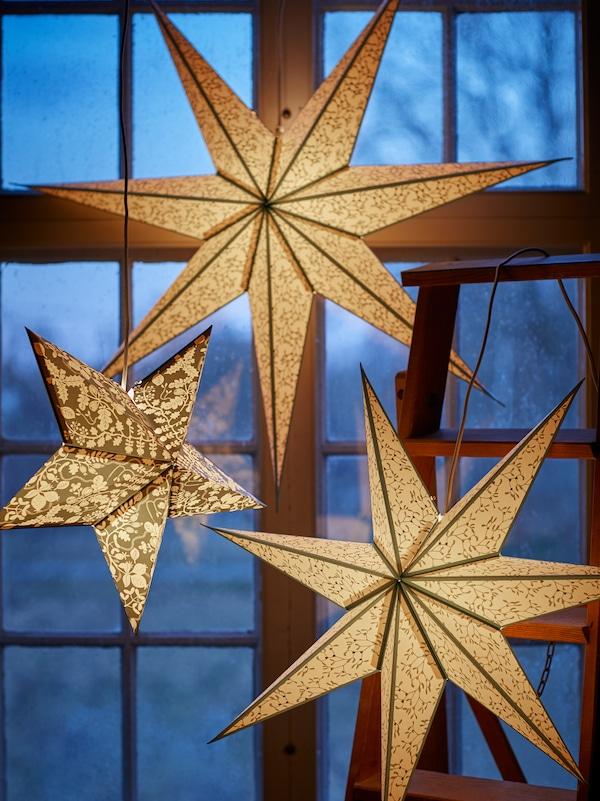 Kolme valaistua tähtien muotoista STRÅLA -lampunvarjostinta, eri malleja ja kokoja, riippuvat ikkunassa illalla.