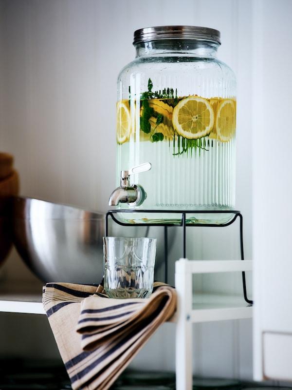 Sur une tablette blanche, une fontaine à eau VARDAGEN remplie d'eau aromatisée de tranches de citron et d'herbes posée sur son support, un verre en dessous du robinet.