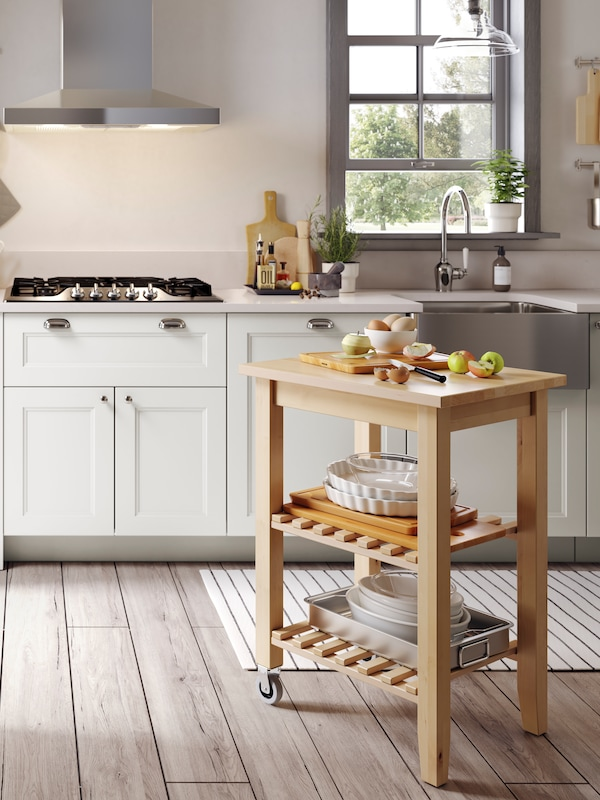 A BEKVÄM kitchen trolley on castors is standing by a stove, apples are being peeled and sliced on its top surface.