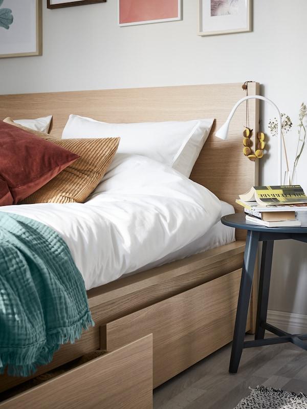 Une table de la collection de tables gigognes KRAGSTA placée près d'un lit haut MALM à quatre tiroirs et des linges de lit ÄNGSLILJA blancs.