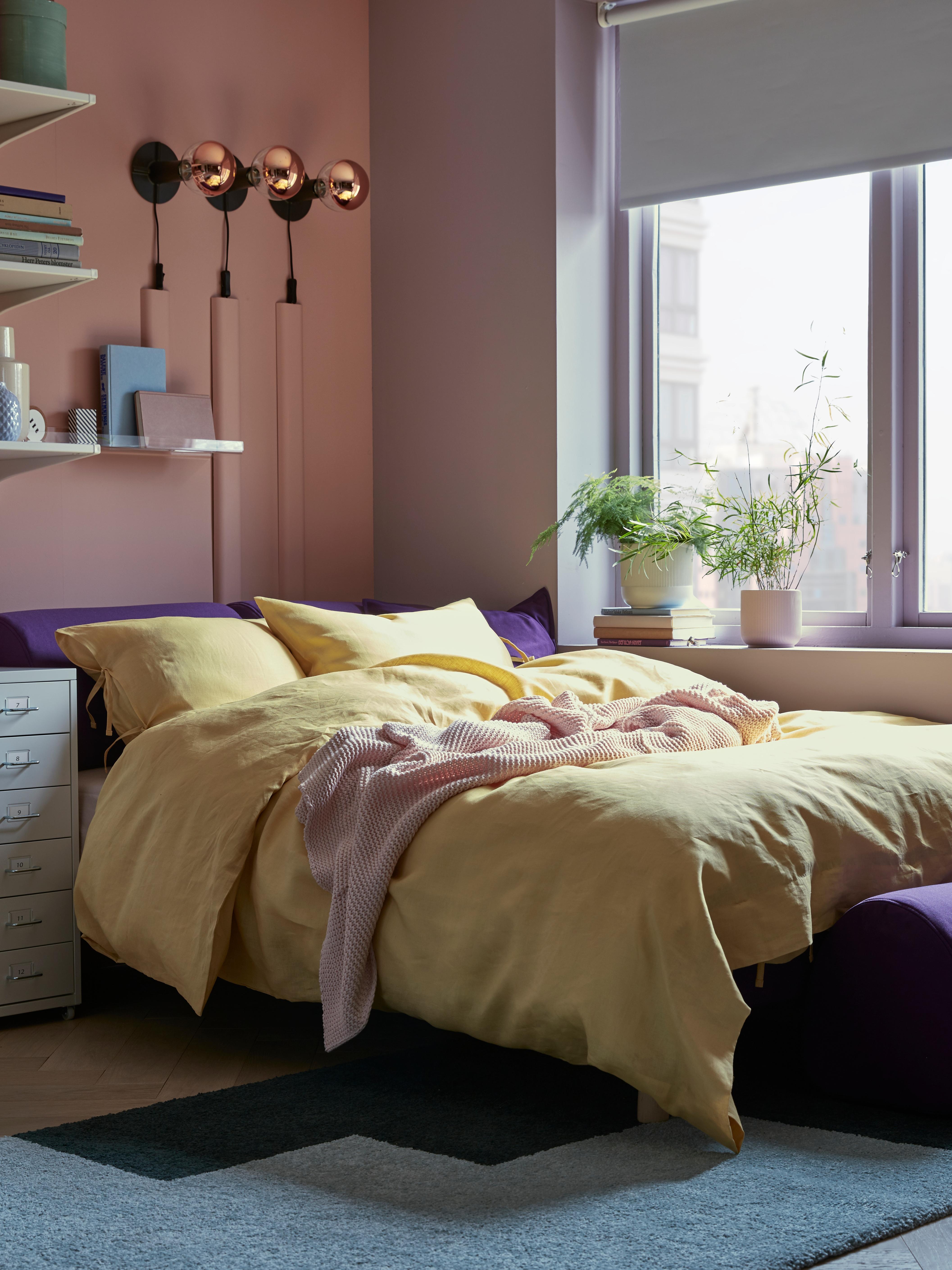 Pellavaiset PUDERVIVA-pussilakana ja -tyynyliinat violetilla vuodesohvalla vaaleanpunaisessa huoneessa ikkunan vieressä.