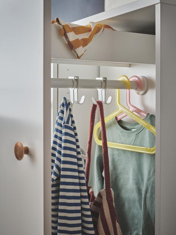 An einem weissen SMÅSTAD Kleiderschrank ist der Auszug mit einer oberen Schublade und Haken und Bügeln ausgezogen. An den Haken und Kleiderbügeln hängen Kleidung und eine Tasche.