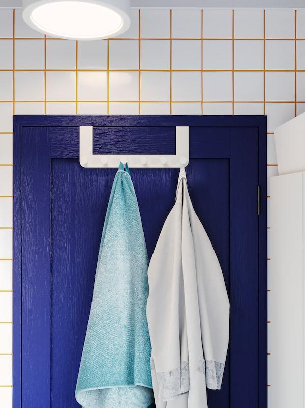 Penyangkut berwarna putih untuk pintu digantung pada pintu berwarna biru, dengan tuala dan jubah mandi pada pencangkuk. Jubin berwarna putih dan turap berwarna kuning.