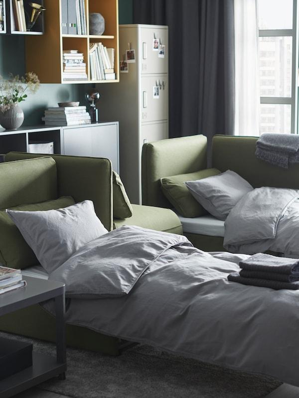 Ein Wohnzimmer mit zwei grünen VALLENTUNA Bettsofas, die als Betten zurechtgemacht sind.
