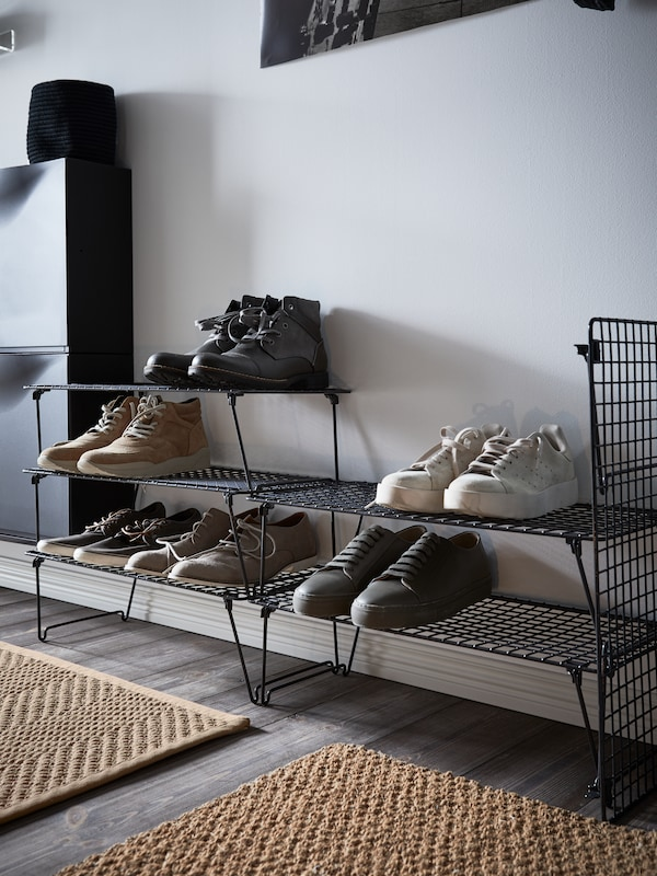 GREJIG shoe racks, with shoes and boots, stand in a hallway. Some shoe racks are stacked on top of each other.