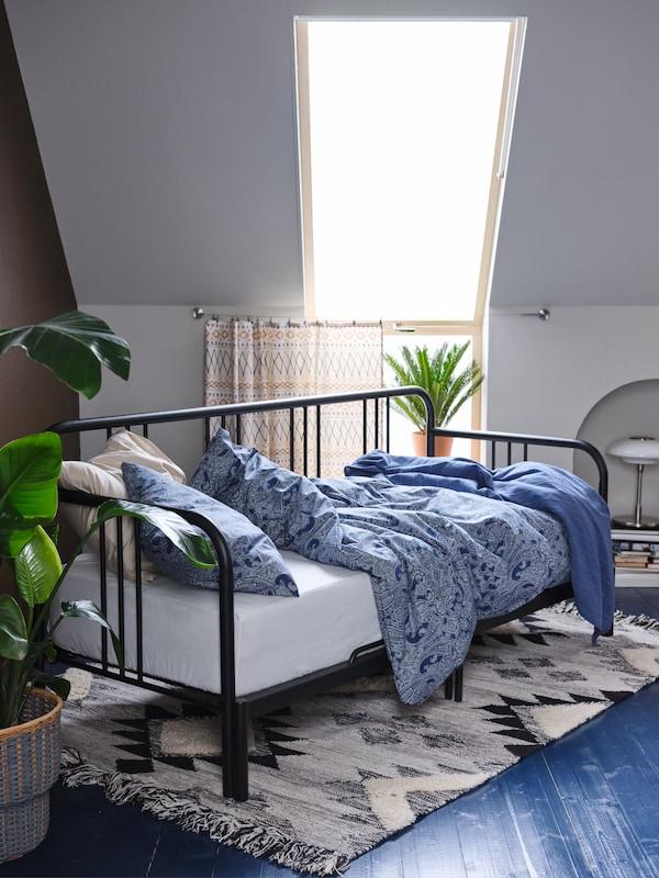 غرفة ذات أرضية زرقاء ونافذة كبيرة وسرير نهاري FYRESDAL أسود عليه غطاء لحاف وكيس وسادة لون أزرق.
