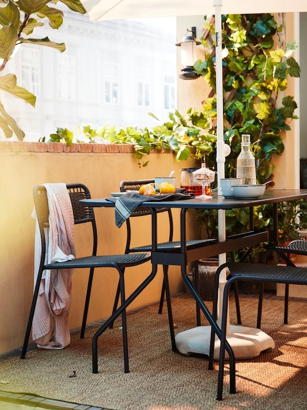 Ein dunkelgraues Essplatzset auf einem Balkon. Auf dem Tisch sind Obst, Tee, Wasser und Geschirr zu sehen.