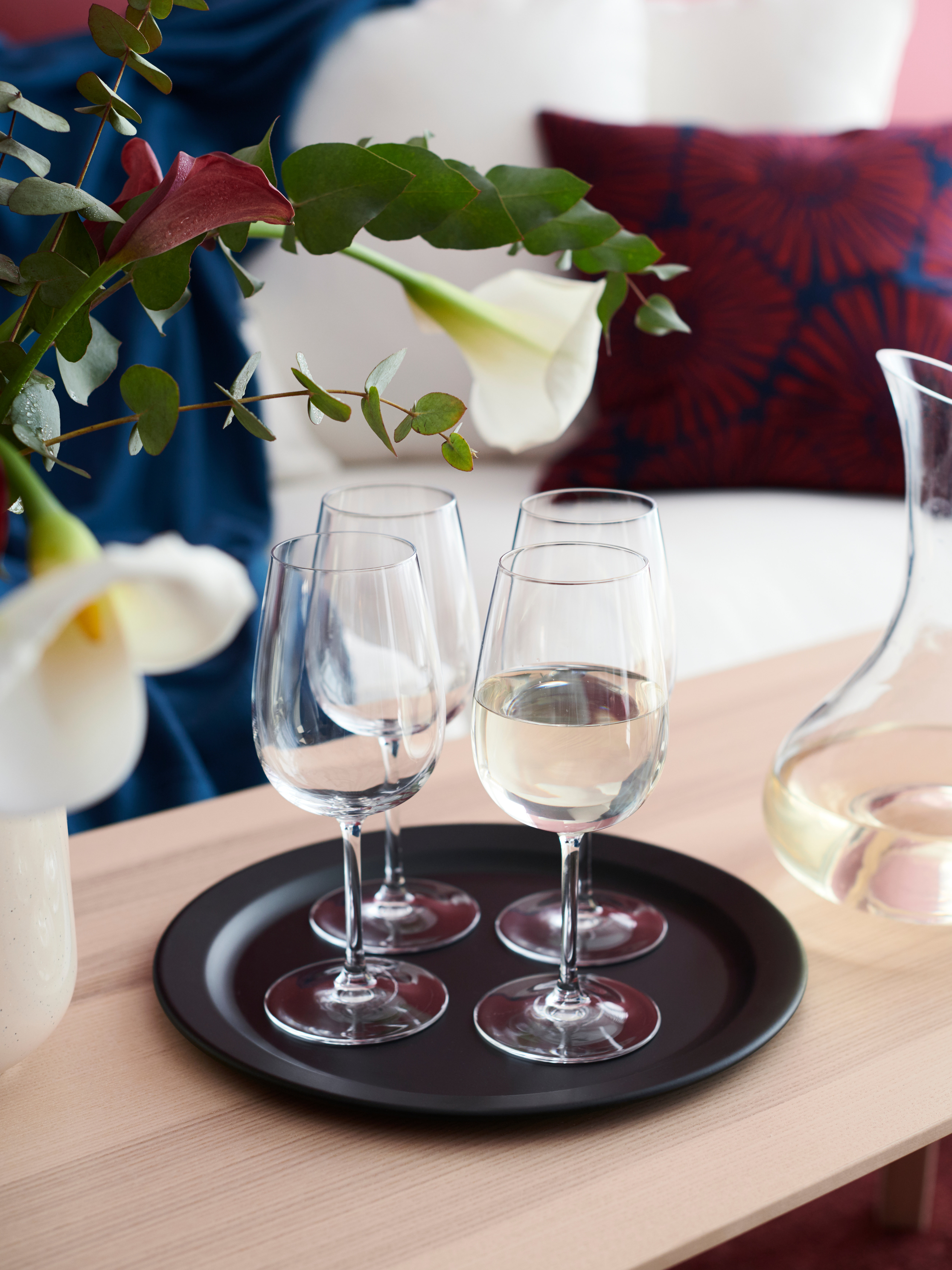 Four STORSINT white wine glasses on a round black serving platter with flowers in the foreground.