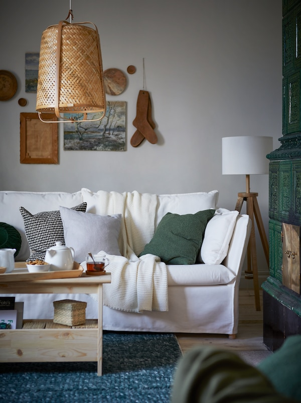 아늑한 방 안에 쿠션과 담요가 놓여 있는 화이트 3인용 BACKSÄLEN 박셀렌 소파가 있어요.
