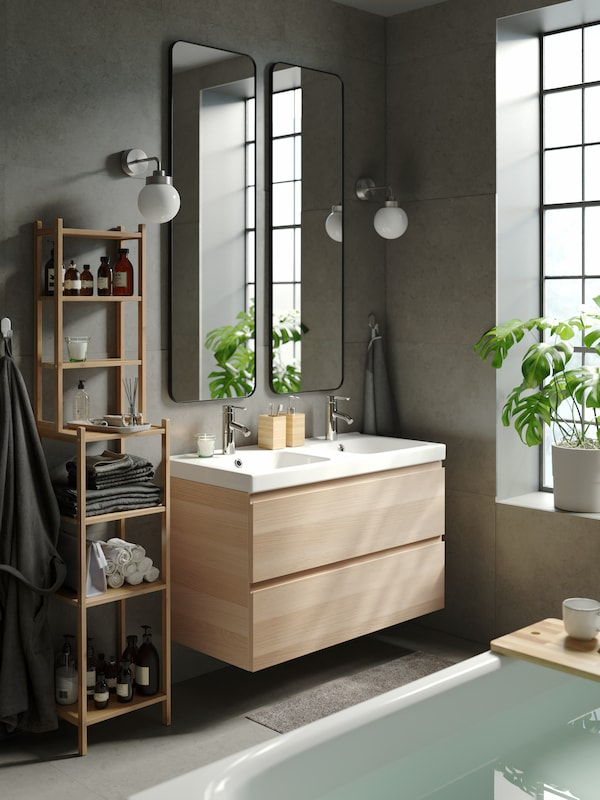 A contemporary, bright bathroom with grey walls, two LINDBYN mirrors above a wash-stand with double wash-basins and drawers.