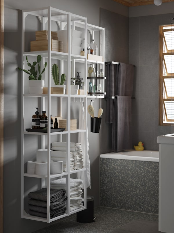 Baño en gris cun estante grande branco e un estante xiratorio negro. Sobre os estantes hai plantas, toallas e caixas.