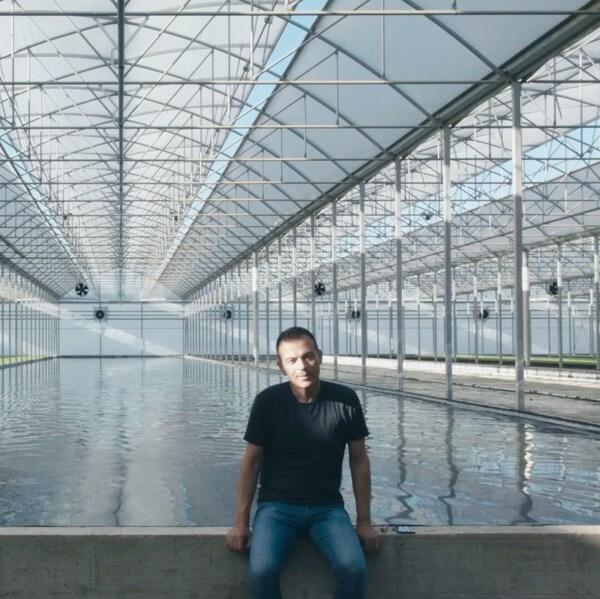 유리 건물 속 수영장 가장자리에 앉아 있는 남자.