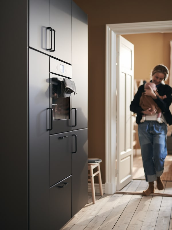 أم تحتضن طفلها وهي تدخل المطبخ، وتقترب من جدار من الخزائن بواجهات KUNGSBACKA.