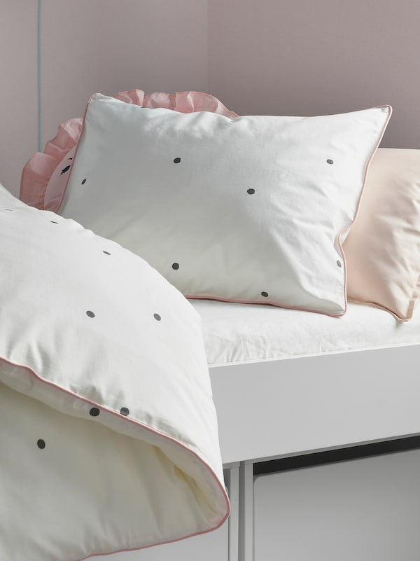 The head of a bed with a pillow and duvet in a white/pink VÄNKRETS quilt cover and pillowcase with a dot pattern.