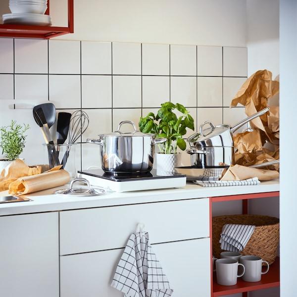 Et hvidt ENHET køkken med gryder og madlavningsredskaber på bordet.