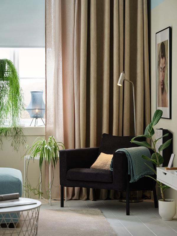 Lænestol, beige gardiner, hvide mørklægningsrullegardiner, beige mørklægningsgardiner, planter og en gulv-/læselampe.