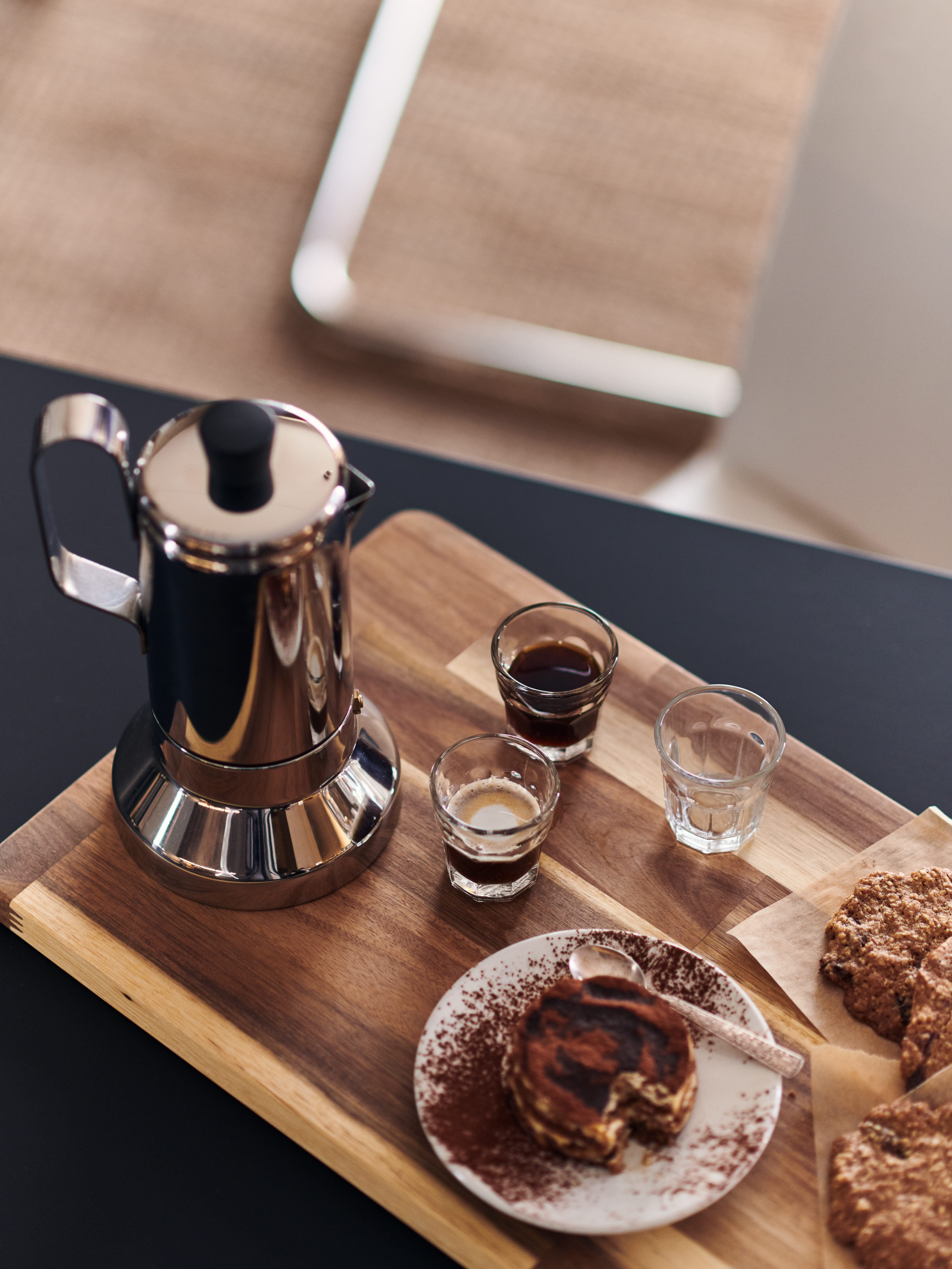 A METALLISK espresso maker, POKAL glasses, a cake and biscuits are on a SMÅÄTA chopping board on a kitchen countertop.
